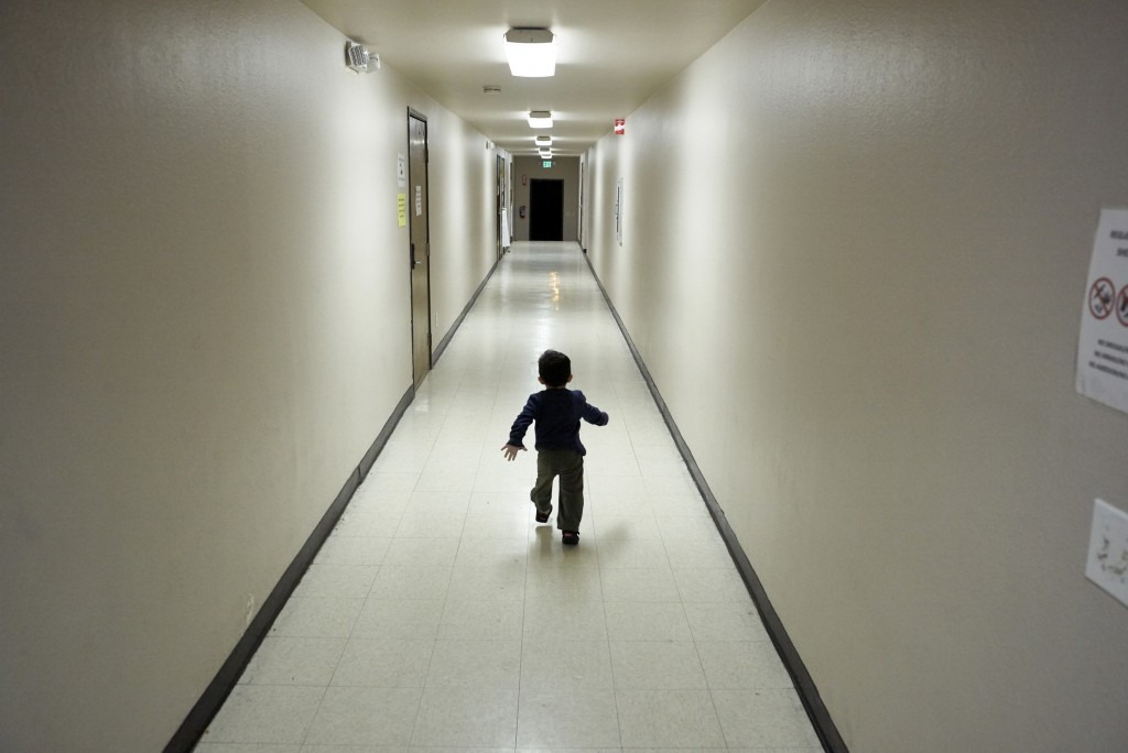 FILE - In this Dec. 11, 2018, file photo, an asylum-seeking boy from Central America runs down a hallway after arriving from an immigration detention ...