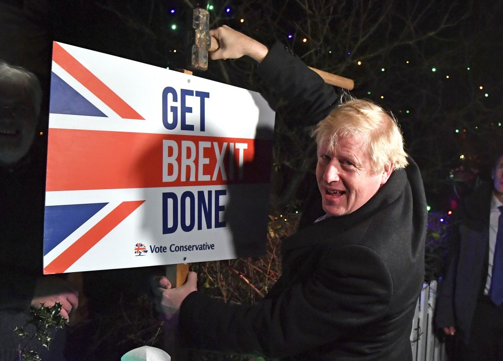 FILE - In this Wednesday, Dec. 11, 2019 file photo, Britain's Prime Minister and Conservative party leader Boris Johnson poses as he hammers a &qu...