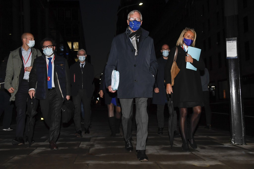 EU Chief negotiator Michel Barnier, centre, wears a face mask as he leaves The Westminster Conference Centre in London, Thursday, Oct. 22, 2020. Barni...