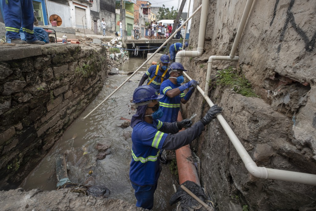 Men work to install a sewage system at the Americanopolis community, located near the Pinheiros River in Sao Paulo, Brazil, Thursday, Oct. 22, 2020. A...