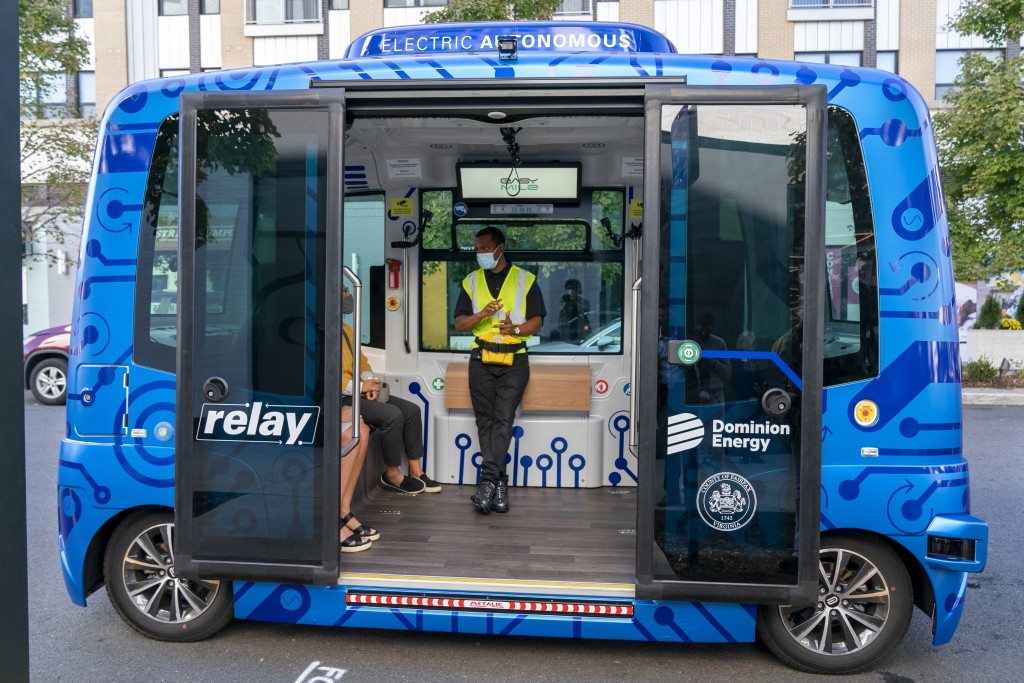 Deployment Manager Jason Peres, center, explains how Relay, an electric autonomous vehicle, works to new riders in Fairfax, Va., Thursday, Oct. 22, 20...
