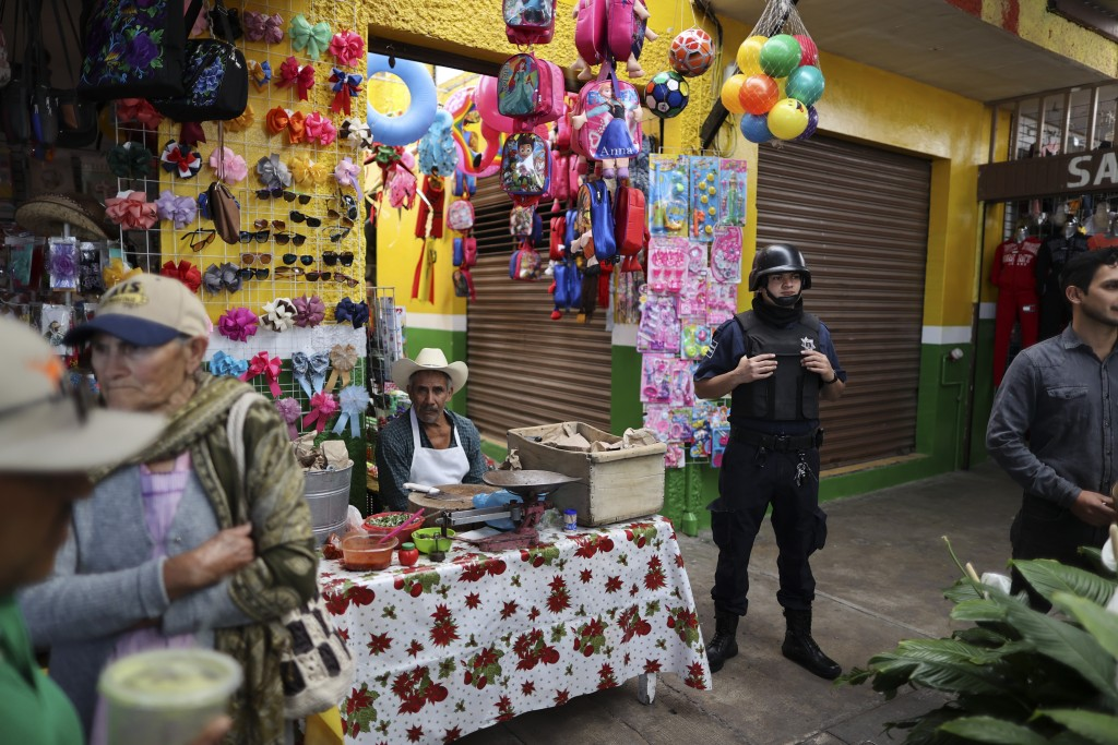 FILE - In this Feb. 10, 2020 file photo, a policeman stands guard as the city mayor attends an event to inaugurate renovated sections of the market, w...