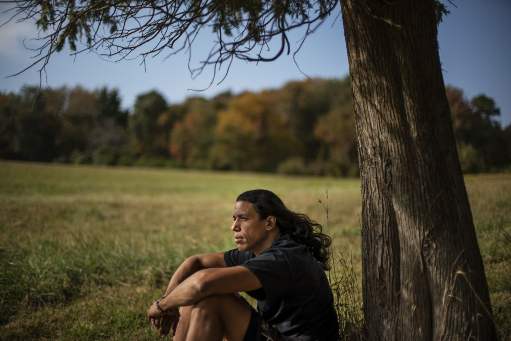 """Annawon Weeden, 46, a member of the Mashpee Wampanoag Tribe, sits for a portrait outside his home in Oakdale, Conn., Friday, Sept. 25, 2020. """"How do y..."""