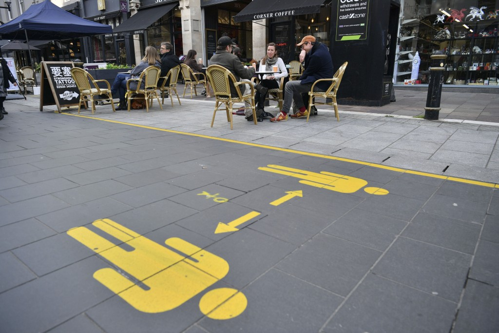 """Customers sit in the outdoor seating of bars and cafes in Cardiff prior to Wales entering a """"firebreak"""" lockdown, Friday, Oct. 23, 2020. A police forc..."""