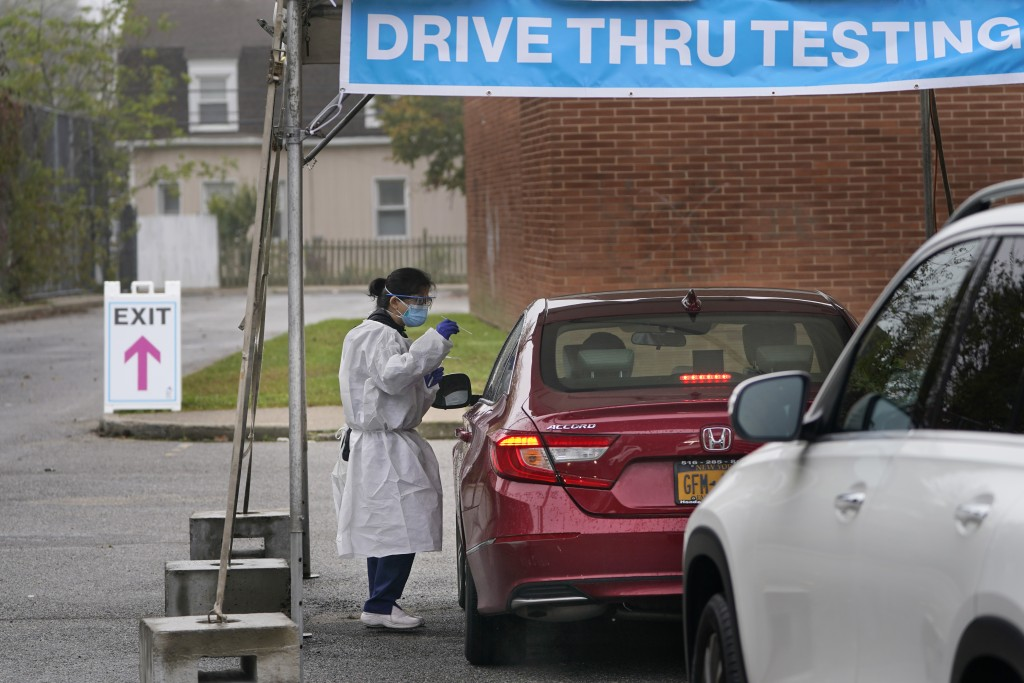 FILE - In this Oct. 21, 2020, file photo, medical personnel prepare to administer a COVID-19 swab at a drive-through testing site in Lawrence, N.Y. Th...