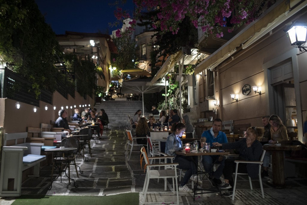 People sit outside a bar in the Plaka district of Athens, on Friday, Oct. 23, 2020. Greece's government will impose from Saturday a nightly curfew in ...