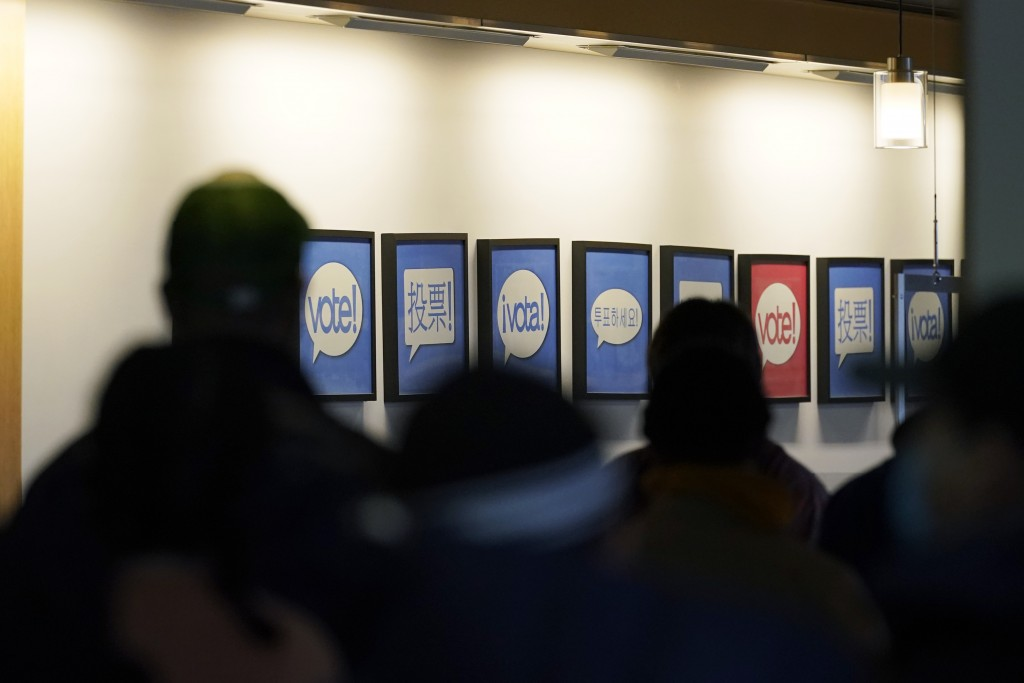FILE - In this Oct. 23, 2020, file photo people lined up to vote or register to vote are shown next to signs in different languages at the King County...
