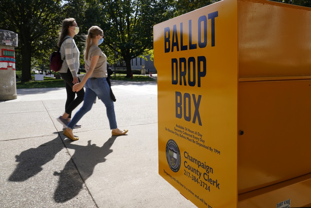 FILE - In this Oct. 6, 2020, file photo, University of Illinois students walk past a mail-in ballot drop box that sits on the northwest corner of the ...
