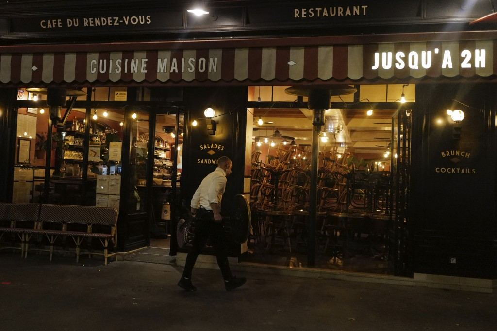 A waiters cleans the terrace of a restaurant before the nightly curfew due to the restrictions against the spread of the Coronavirus disease, in Paris...