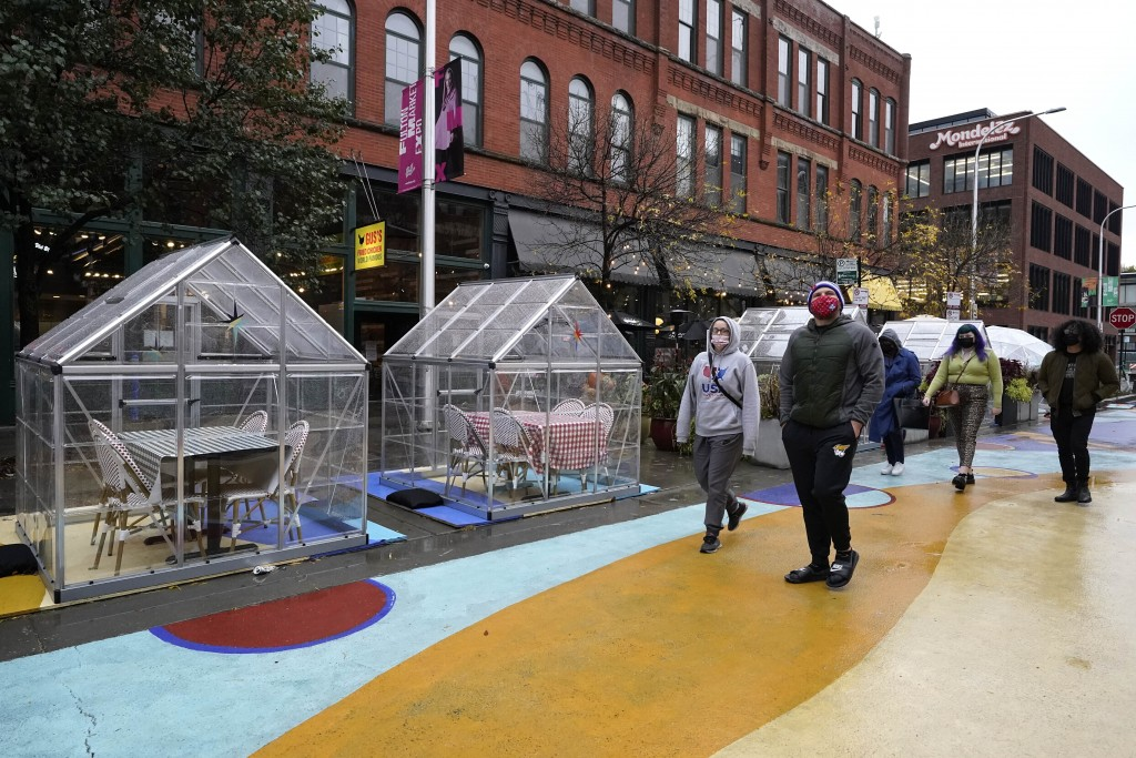 FILE - In this Oct. 18, 2020, file photo, people walk by outdoor plastic dining bubbles on Fulton Market in Chicago. The United States is approaching ...