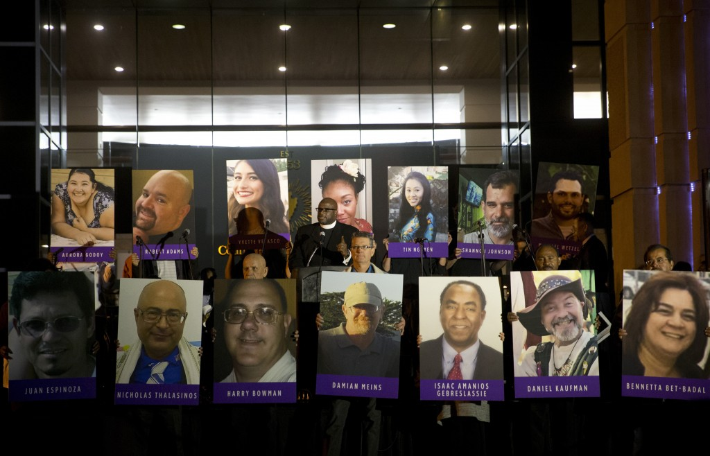 FILE - In this Dec. 7, 2015, file photo, San Bernardino County employees hold up photos of the San Bernardino shooting victims during a candlelight vi...