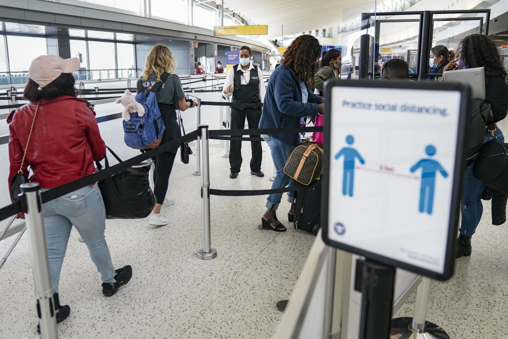 FILE - In this Oct. 20, 2020, file photo, transportation Security Administration personnel and travelers observe COVID-19 transmission prevention prot...