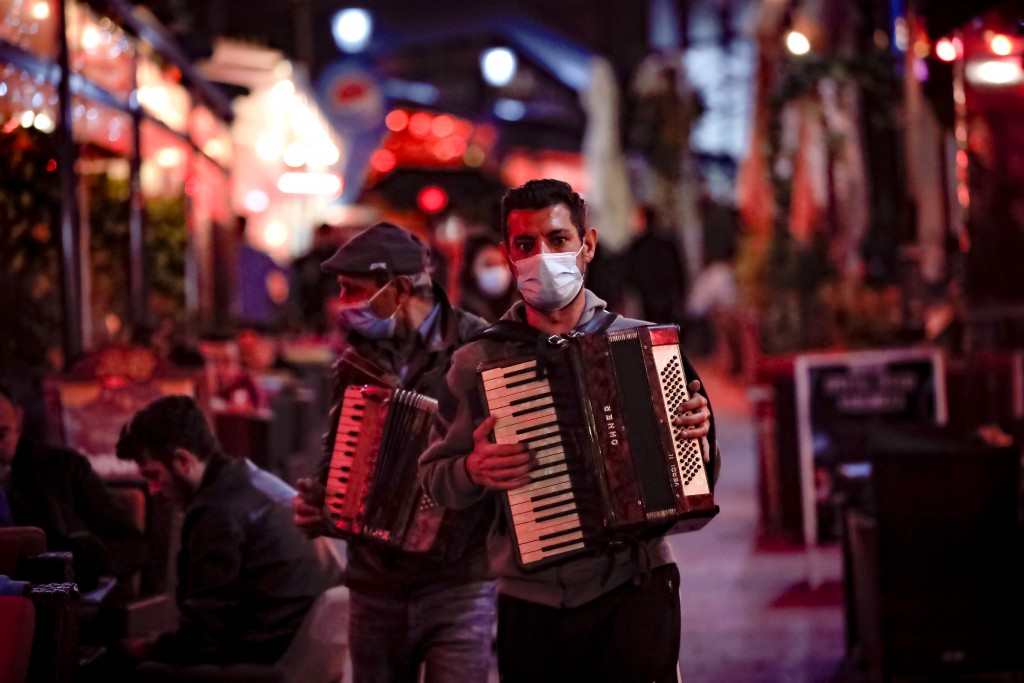 Entertainers playing accordions, wearing face masks for protection against the COVID-19 infection walk by restaurants in the old part of Bucharest, Ro...