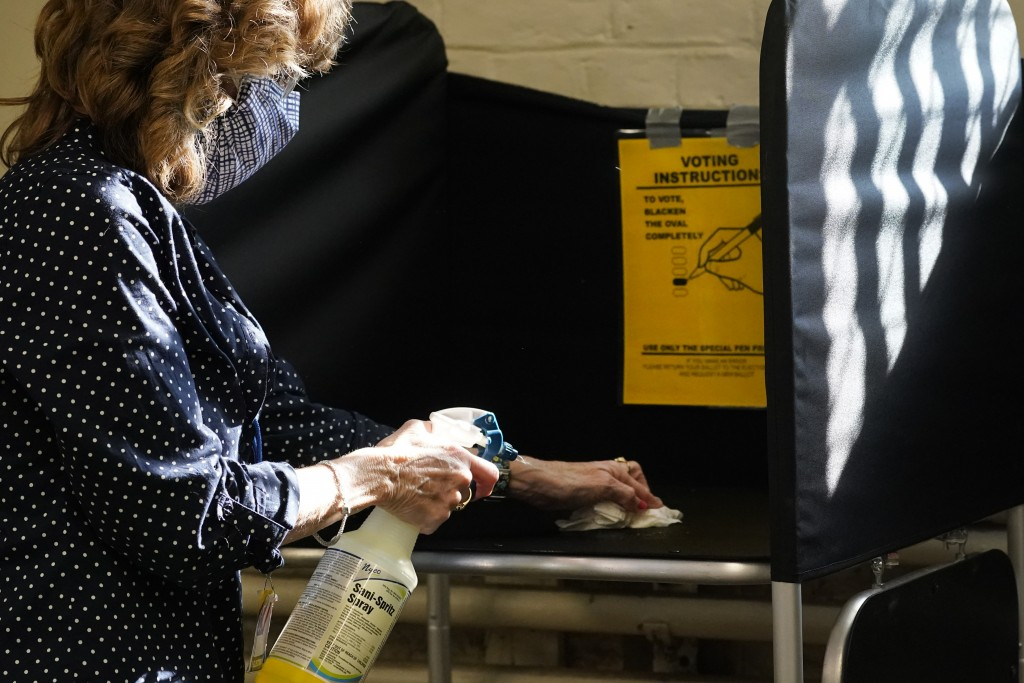 FILE - In this Oct. 22, 2020, file photo, election clerk Cheryl Lupi sanitizes a voting booth inside Haverhill City Hall during early in-person voting...