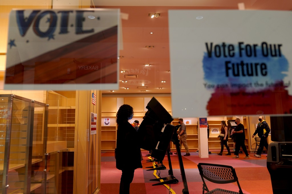 FILE - In this Oct. 17, 2020, file photo, a woman casts her ballot on the first day of early voting in a recently-shuttered store at Oak Park Mall in ...