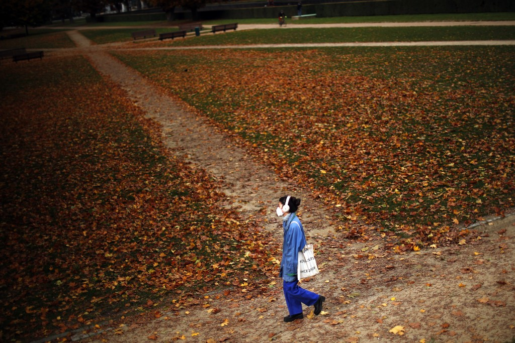 A woman, wearing a face mask to prevent the spread of the coronavirus COVID-19, walks along Cinquantenaire park in an autumn day in Brussels, Friday, ...