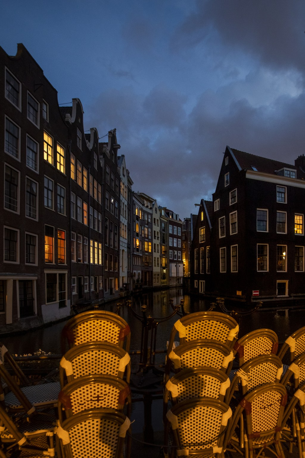 Terrace chairs are stacked outside a bar in the historic center of Amsterdam, Netherlands, Friday, Oct. 23, 2020. Dutch bars and restaurants were clos...