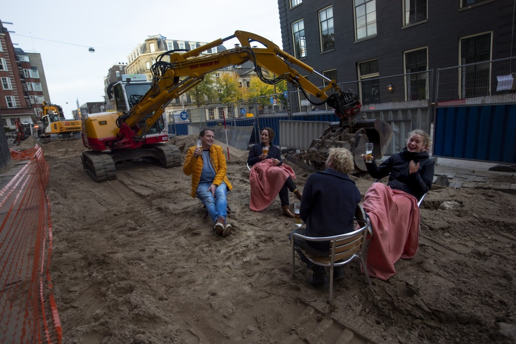 People enjoy a beer on an improvised beach terrace during road construction works outside a bar in Amsterdam, Netherlands, Friday, Oct. 23, 2020. Dutc...