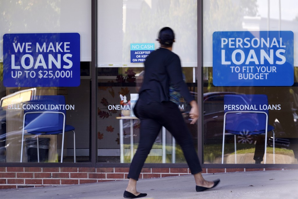 A woman walks past a personal finance loan office Thursday, Oct. 1, 2020, in Franklin, Tenn.  Consumers, by and large, improved their credit profile d...