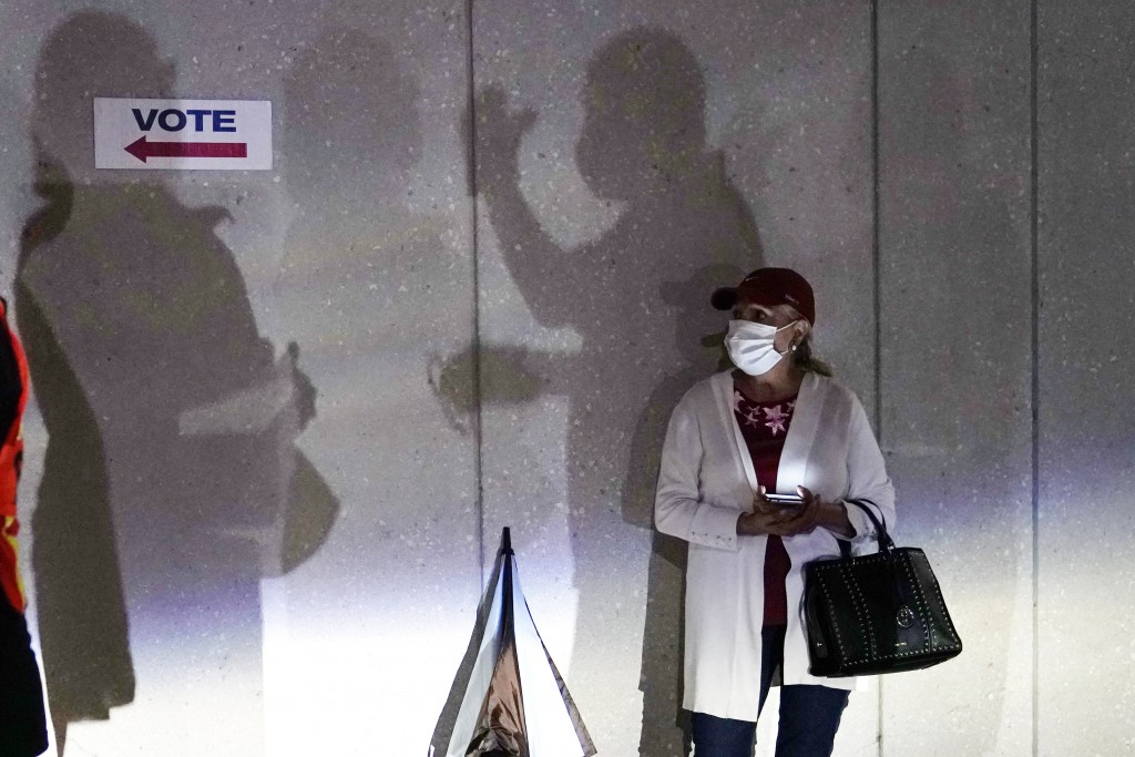 FILE - In this Oct. 19, 2020, file photo a woman waits to vote in Miami. Election officials are on high alert amid fears that U.S. polling stations co...
