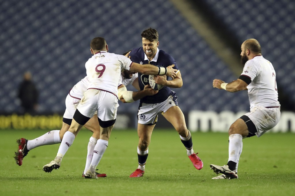 Scotland's Adam Hastings, center, is tackled by Georgia's Vasil Lobzhanidze battle for the ball during the Autumn International rugby match at BT Murr...
