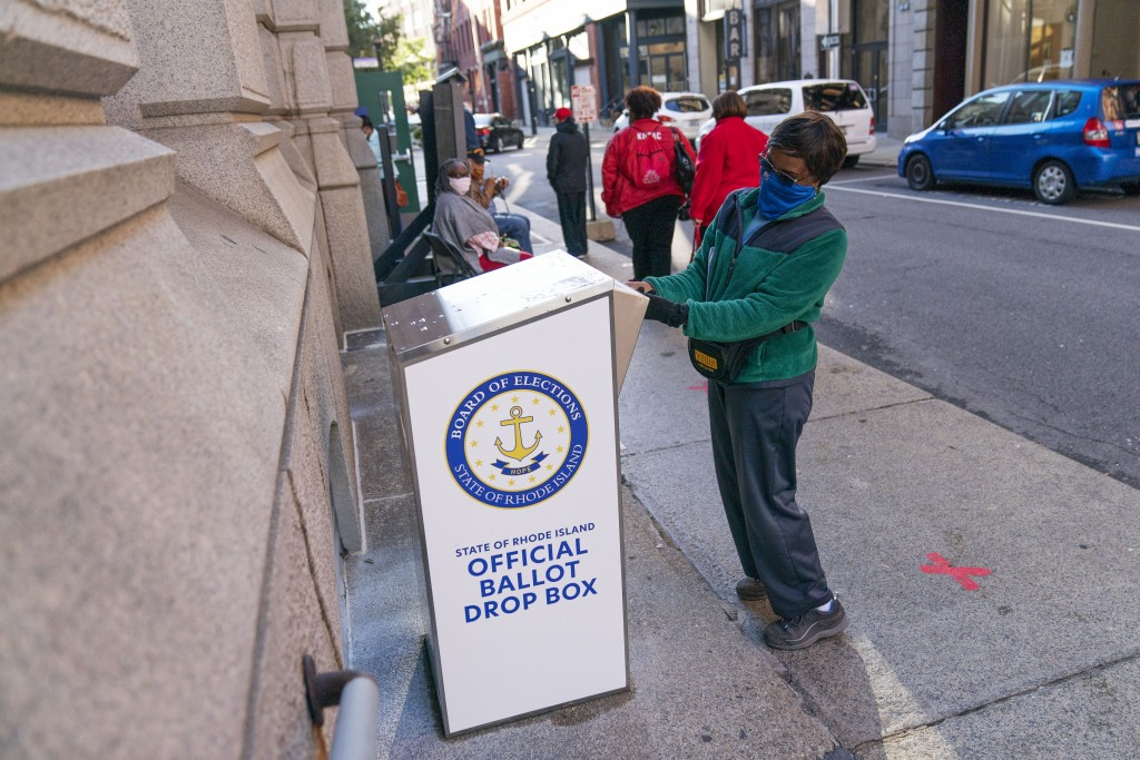 FILE - In this Oct. 14, 2020, file photo, Eva Abodoadji drops off a mail ballot into an official ballot drop box as voters wait in line at City Hall a...