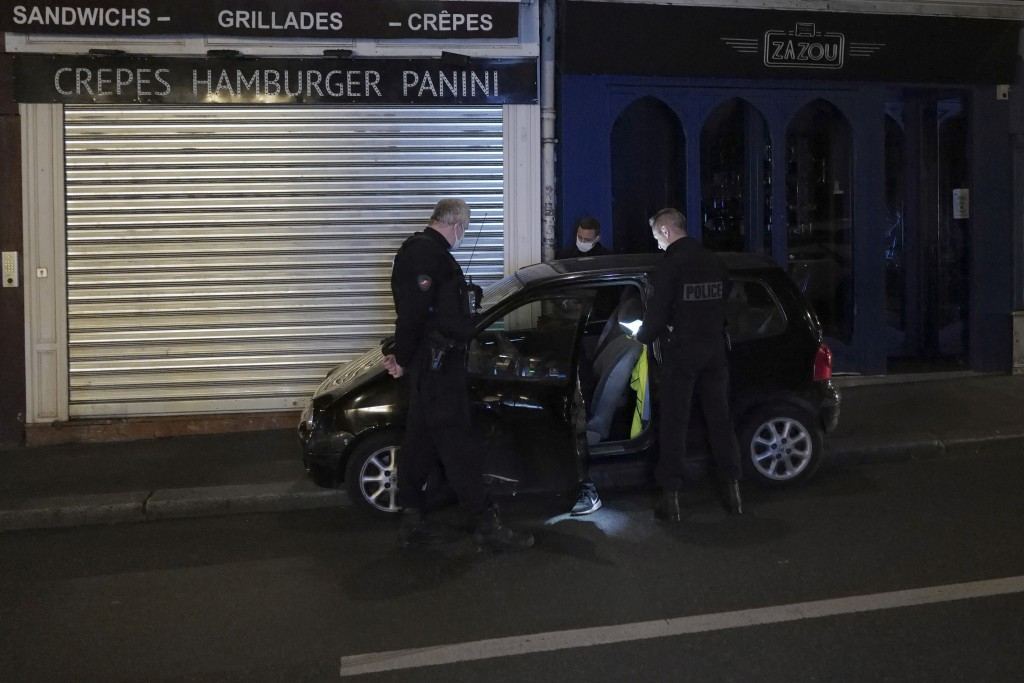 French Police officers check a car just after the nightly curfew due to the restrictions against the spread of the Coronavirus disease, in Paris, Fran...