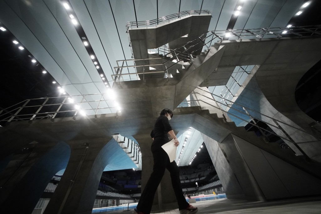 A woman walks by the diving platform at Tokyo Aquatics Center after its grand opening ceremony Saturday, Oct. 24, 2020, in Tokyo. The Tokyo 2020 organ...