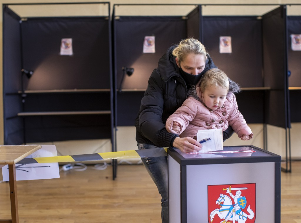 A woman wearing a face mask to protect against the coronavirus, with a child, casts her ballot at a polling station during the second round of a parli...