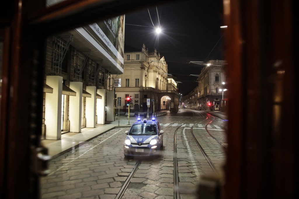 A police car follows a tram streetcar running along an empty street by the La Scala theater, in Milan, northern Italy, early Sunday, Oct. 25, 2020. Si...