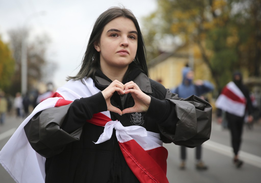 A woman draped in an old Belarusian national flag gestures during an opposition rally to protest the official presidential election results in Minsk, ...