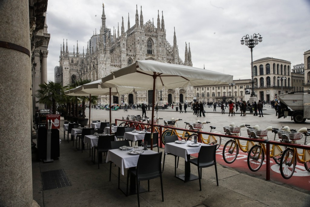 FILE - In this Wednesday, Oct. 21, 2020 file photo, empty tables of a restaurant in the Duomo Square in Milan, Italy. The coronavirus pandemic is gath...