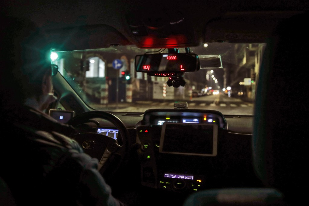 A taxi drives along an empty street in Milan, northern Italy, early Sunday, Oct. 25, 2020. Since the 11 p.m.-5 a.m. curfew took effect last Thursday, ...