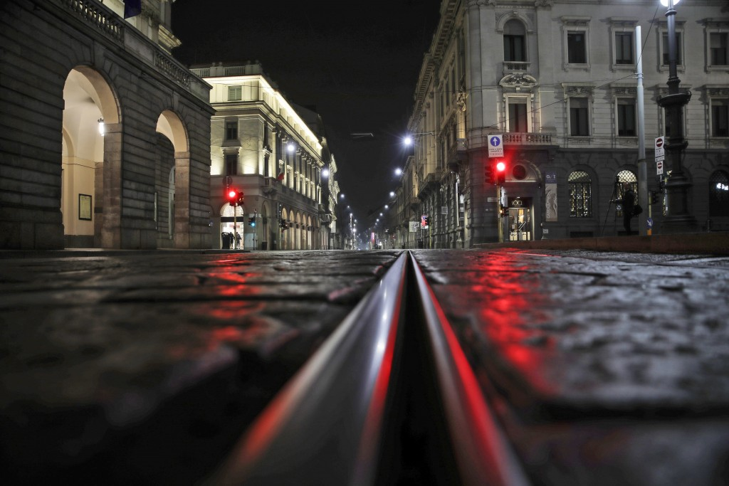 An empty street in front of La Scala opera house is lit by a red traffic light in Milan, northern Italy, early Sunday, Oct. 25, 2020. Since the 11 p.m...