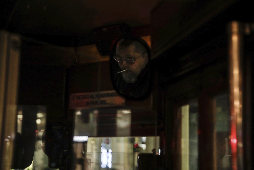 A streetcar driver is reflected in a mirror, top right, as he drives around Milan, northern Italy, early Sunday, Oct. 25, 2020. Since the 11 p.m.-5 a....
