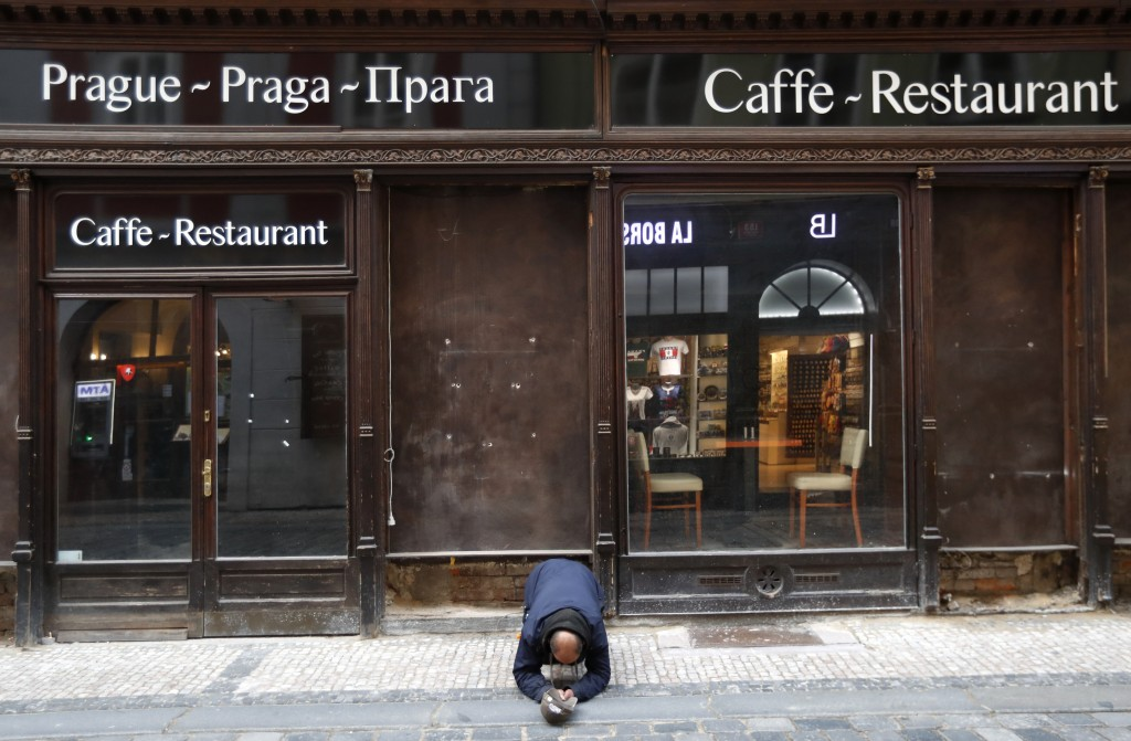 FILE - In this Sunday, Oct. 11, 2020 file photo, a beggar kneels in front of a closed restaurant in downtown Prague, Czech Republic. The coronavirus p...
