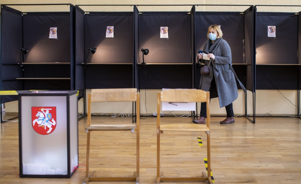 A local resident walks to cast a ballot at a polling station during the second round of a parliamentary election in Vilnius, Lithuania, Sunday, Oct. 2...
