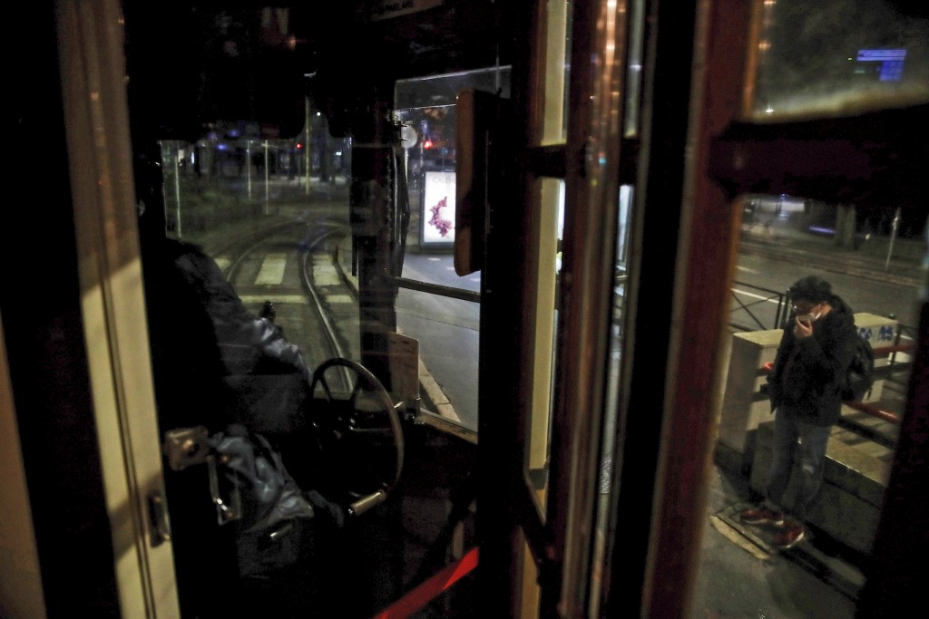 A man who stepped off a tram streetcar, right, waits at a stop as the tram moves on, in Milan, northern Italy, Sunday, Oct. 25, 2020. Since the 11 p.m...