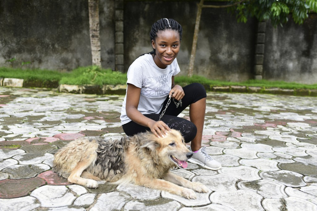 In this photo taken on Wednesday, Oct. 14, 2020, Dodeye Ewa, 16 year play with a dog outside her compound in Calabar, Nigeria. The third child is both...