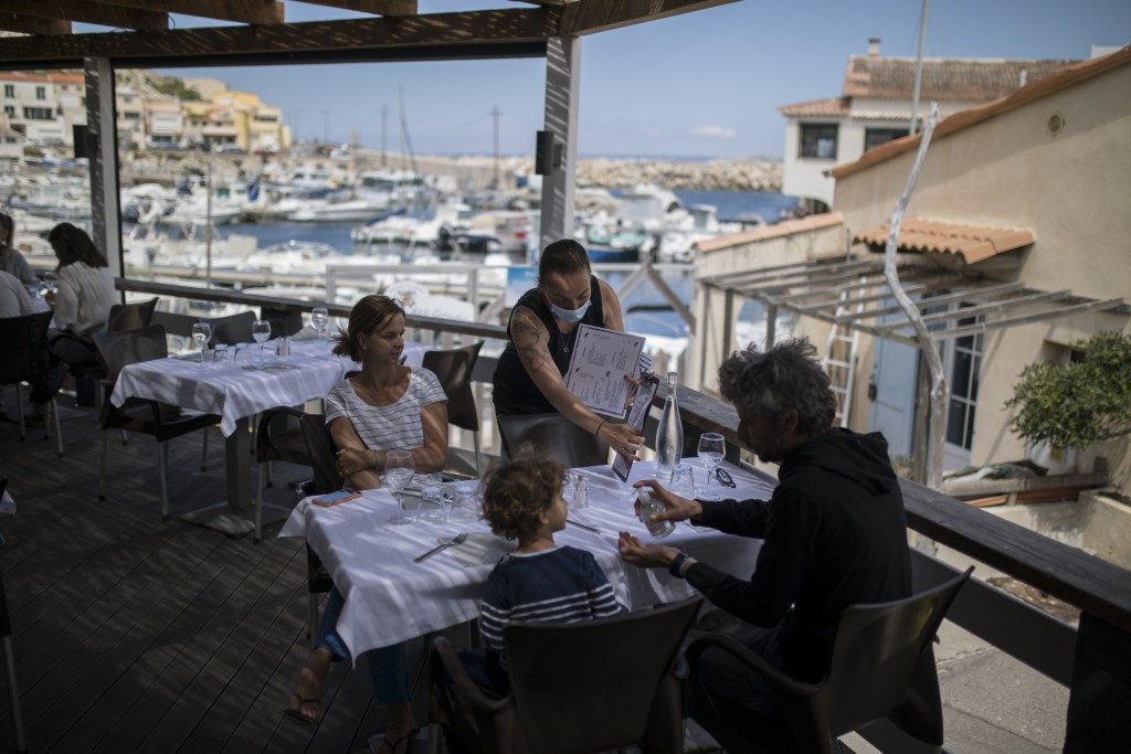 FILE- In this Tuesday, June 2, 2020 file photo, diners apply hand sanitizer provided by staff at a seafood restaurant in Marseille, southern France. T...
