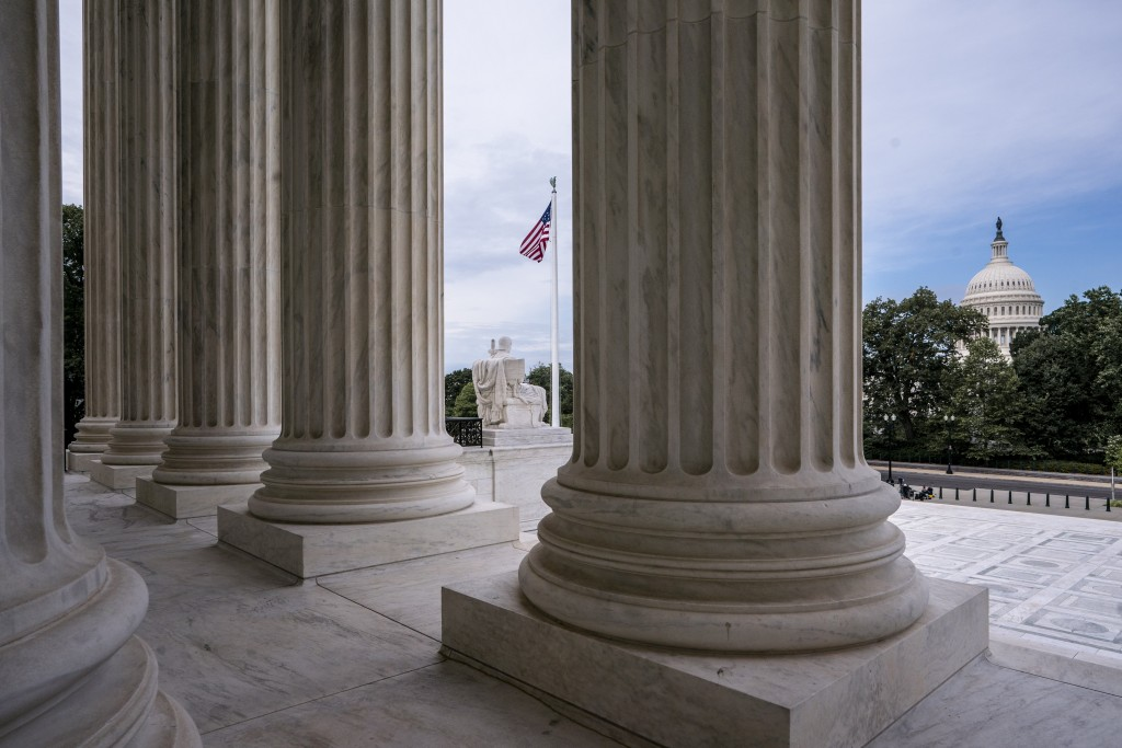 FILE - This June 15, 2020 file photo shows the columns of the Supreme Court with the Capitol at background right in Washington. (AP Photo/J. Scott App...