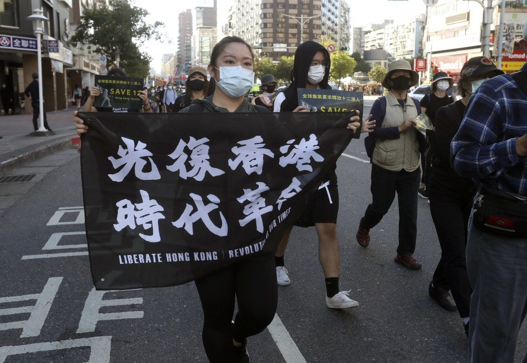 "A protester holds a slogan ""Liberate Hong Kong"" during a march to demand the release of the 12 Hong Kong protesters that have been arrested ..."