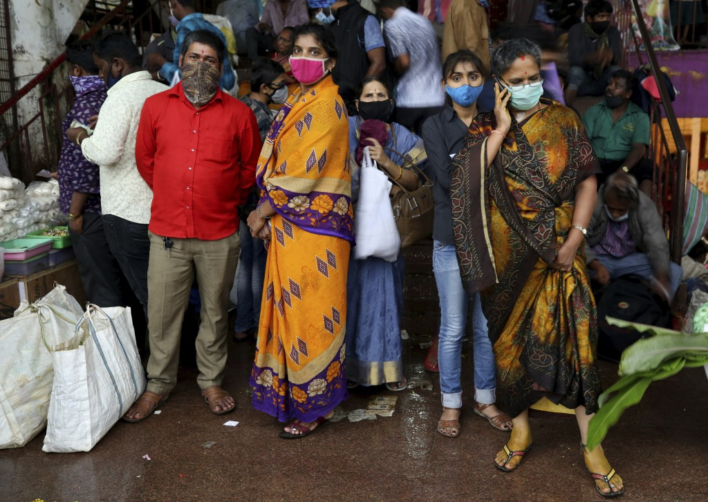People wait to leave as it rains after shopping at a wholesale flower market ahead of the Hindu festival of Dussehra, in Bengaluru, India, Friday, Oct...