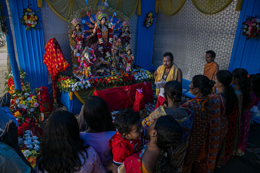 Devotees offer prayers during Durga Puja festival in Gauhati, India, Saturday, Oct. 24, 2020. Weeks after India fully opened up from a harsh lockdown ...