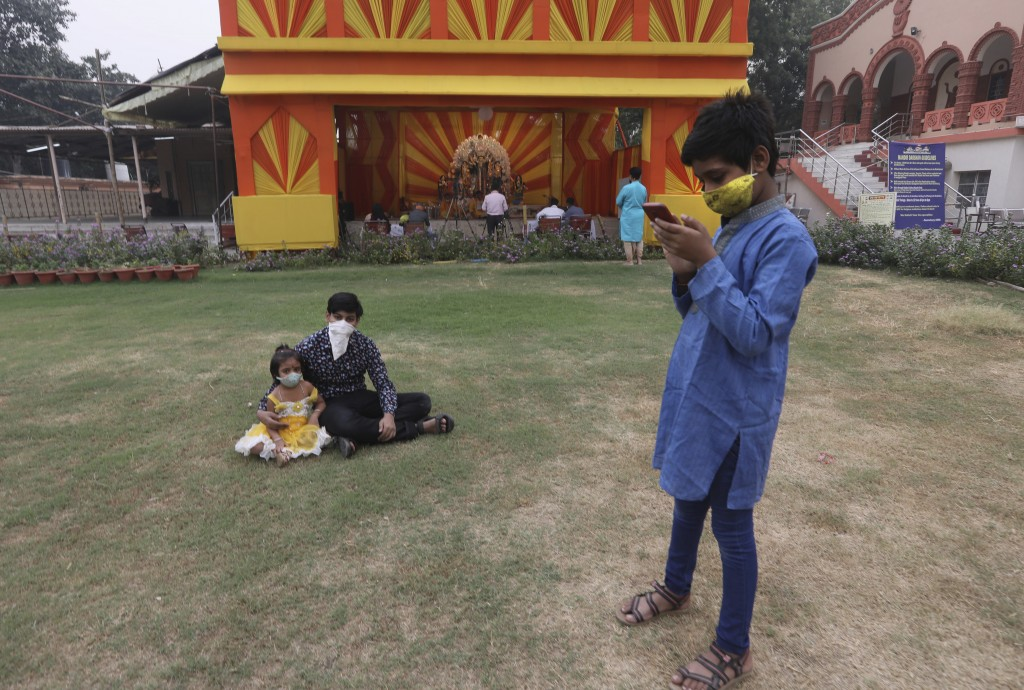A boy checks his mobile phone as his sister and brother sit by a deserted worship venue for Durga Puja festival in New Delhi, India, Thursday, Oct. 22...