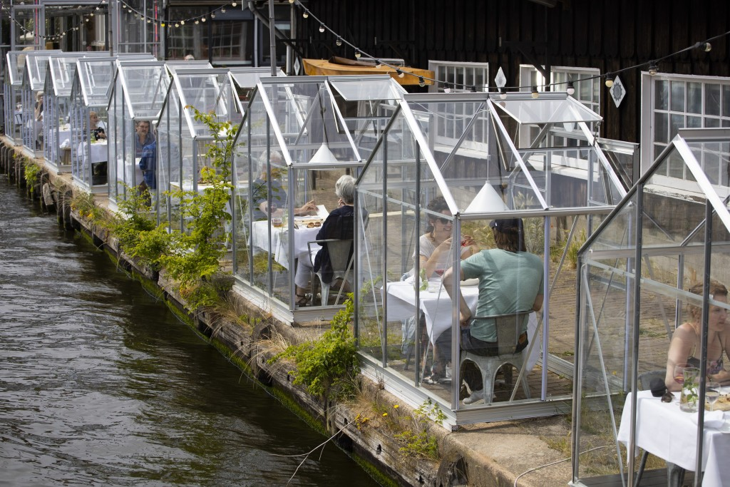 FILE - In this Monday, June 1, 2020 file photo, customers seated in small glasshouses enjoy lunch at the Mediamatic restaurant in Amsterdam, Netherlan...