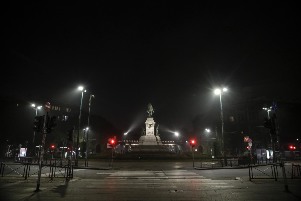 The statue of Italian patriot Giuseppe Garibaldi is lit in the middle of an empty square, in Milan, northern Italy, early Sunday, Oct. 25, 2020. Since...