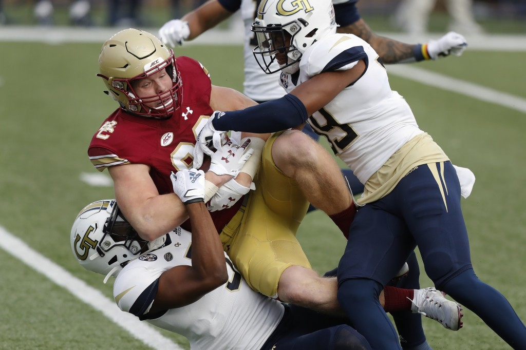 Georgia Tech defensive backs Tre Swilling, bottom, and Wesley Walker, right, tackle Boston College tight end Hunter Long during the first half of an N...