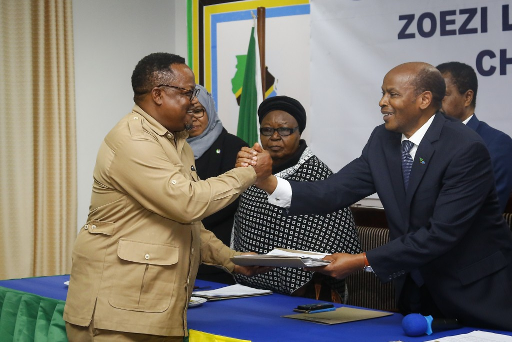 FILE - In this Tuesday, Aug. 25, 2020 file photo, the opposition CHADEMA party's Tundu Lissu, left, hands over his electoral nomination form to Chairm...