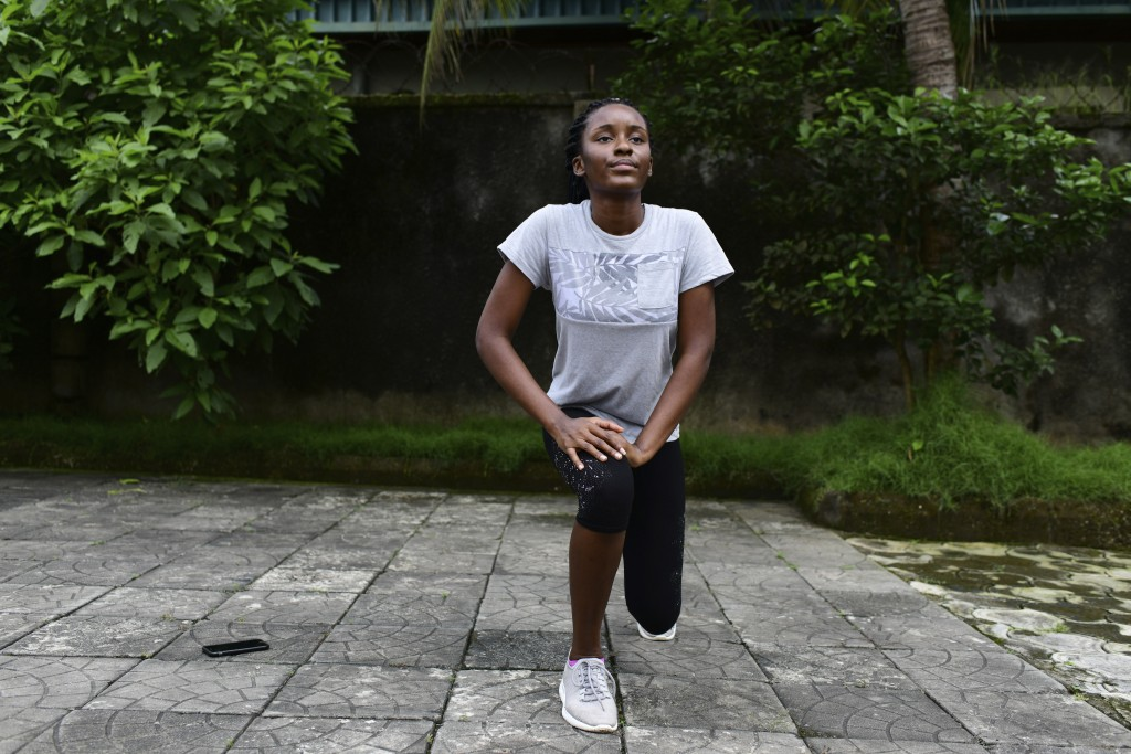 In this photo taken on Wednesday, Oct. 14, 2020, Dodeye Ewa, 16 year old work out inside her family compound in Calabar, Nigeria.  The third child is ...